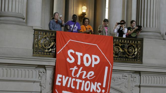 Demonstrators hang a banner inside the rotunda of City Hall during a protest against evictions Friday, May 8, 2015, in San Francisco. Hundreds of protesters rallied at City Hall for a temporary halt to evictions in a popular neighborhood where workers in the booming technology sector are accused of pushing out long-time tenants. A small drum and horn band played outside. (AP Photo/Eric Risberg)